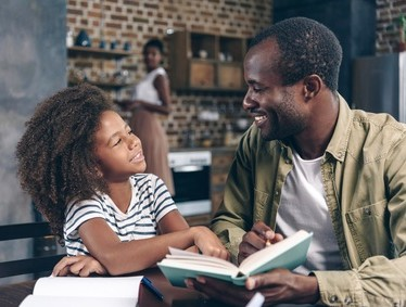 daughter sharing book with father