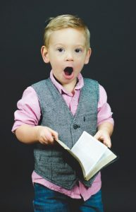 surprised boy with book in hand