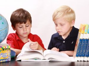 two boys sharing a reference book