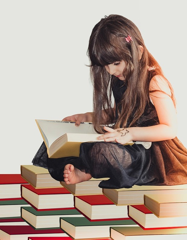 a girl sitting on books and reading