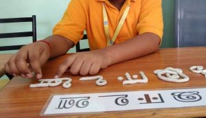 child modeling Hindi letters