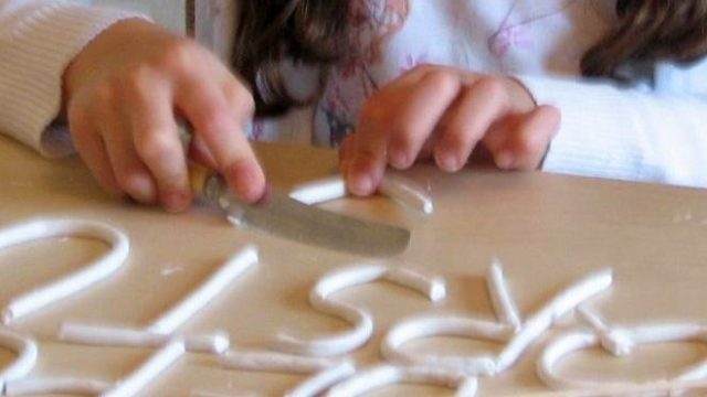 child modeling clay letters