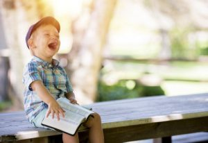 boy with book laughing