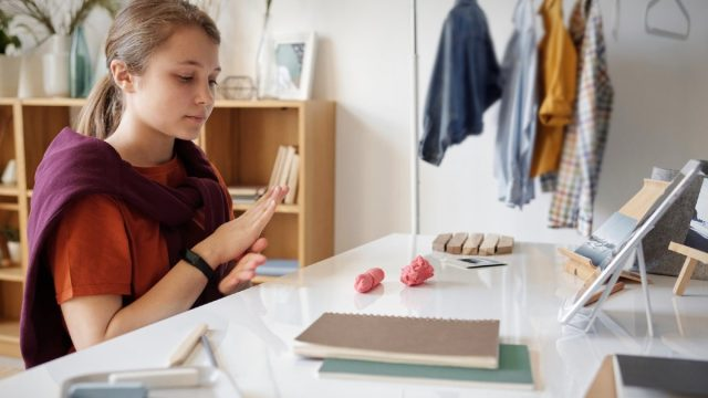 child at desk with modeling clay